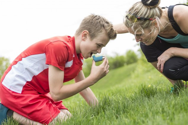 Boy with teacher taking reliever inhaler