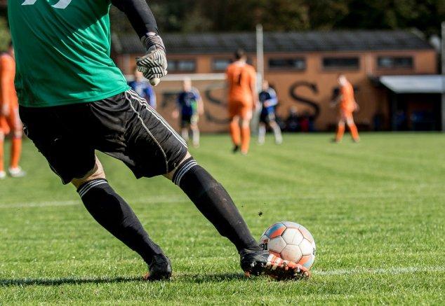 Man kicking football close up