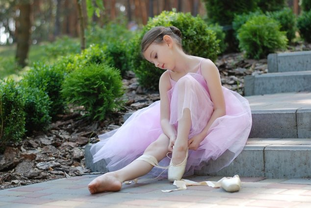 Little girl tying on her ballet shoes