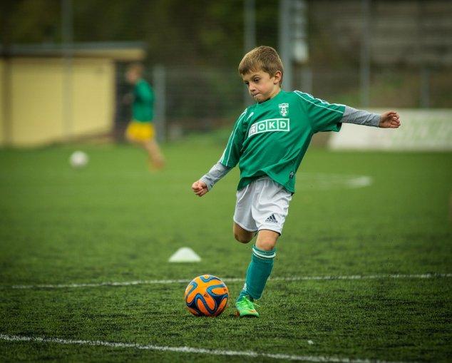 Little boy kicking football