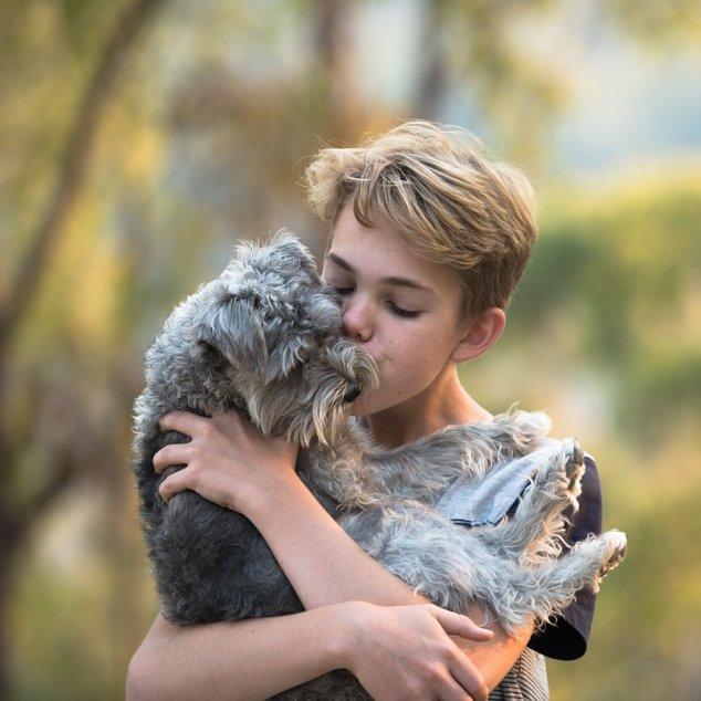 Boy cuddling dog