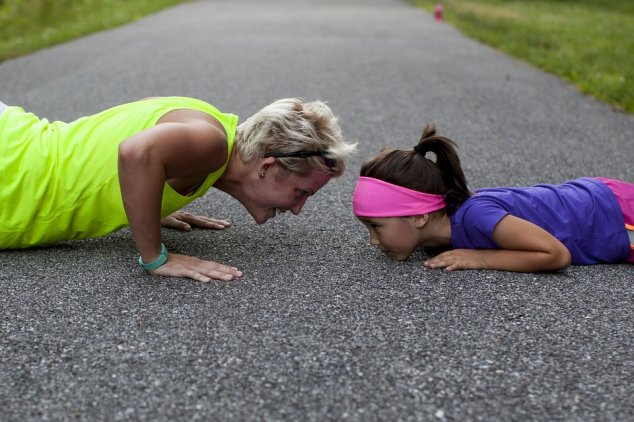 Woman and little girl doing push ups