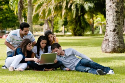 Group of student gathered round a laptop outside
