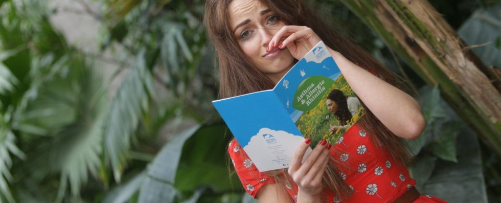 Girl sneezing with hayfever booklet