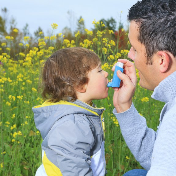Man giving young son reliever inhaler