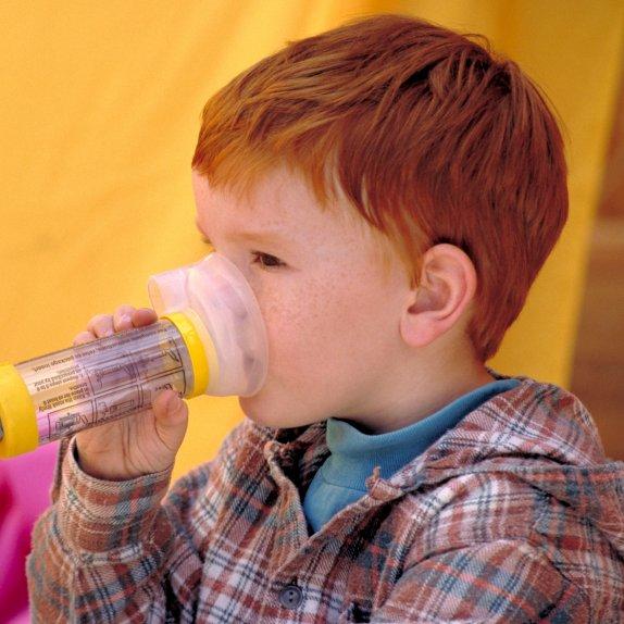 Boy using inhaler with spacer