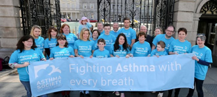 Volunteers holding 'fighting asthma with every breath' banner