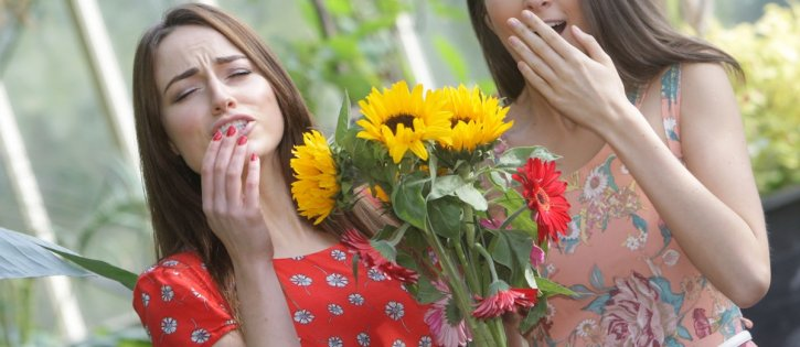 Two girls sneezing due to hay fever