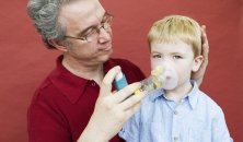 Father helping son with inhaler